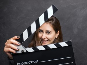 Young woman holding a movie clapboard over black background, studio shot
